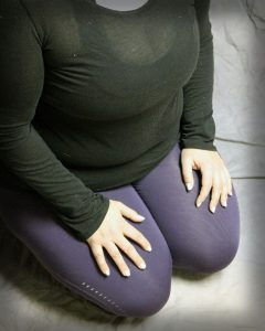 Nicole Havelka sitting in meditation with hands on lap
