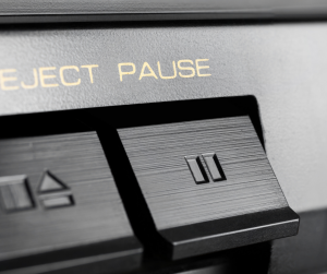 Image of a pause button on an old school stereo with the word pause above the button