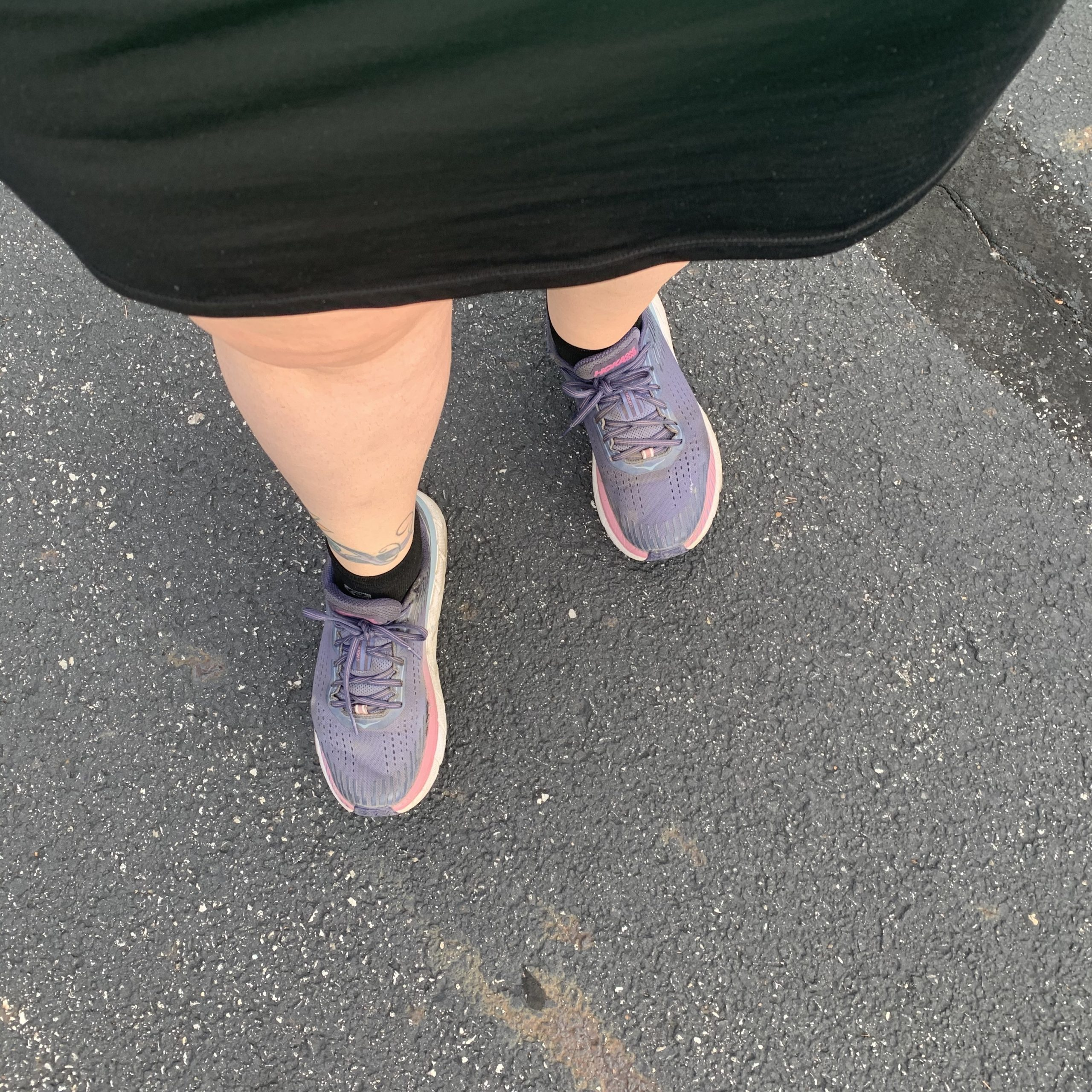 Downshot of a woman walking someone walking in running shoes on the pavement.