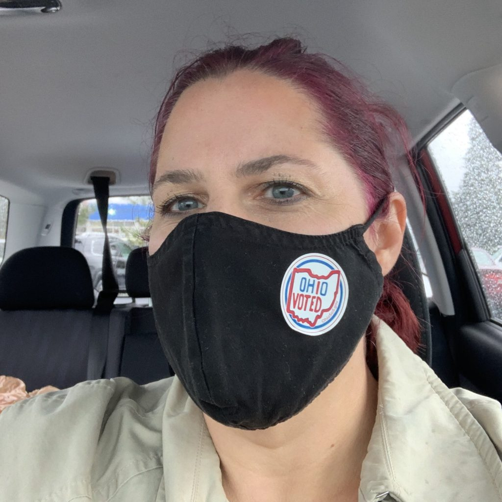 Nicole with black mask with voter sticker on it after voting in general election 2020.