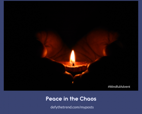 "Image of a single candle being held in the palms of a person's hand with the words at the bottom: #MindfulAdvent, ""Peace in the Chaos"" defythetrend.com/myposts"