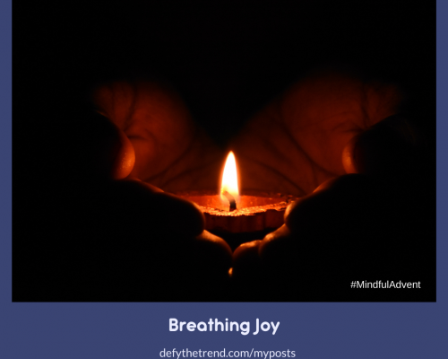 Image of hands holding one lit candle in the darkness with the banner below: Brething Joy, defythetrend.com/myposts