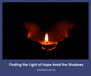 Hands holding a single candle surrounded by darkness