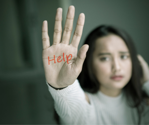 Image of a young caucasian woman with straight brown hair in a white sweater holding her hand up. The word Help is written in red marker on her hand.