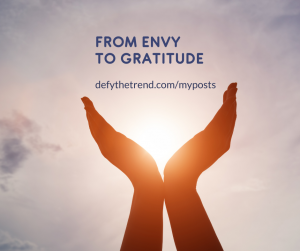"""Picture of hands coming together at the wrists, palms open to either side, the sunset in the background between the hands. words above the hands saying, """"From Envy to Gratitude: defythetrend.com/myposts"""""""